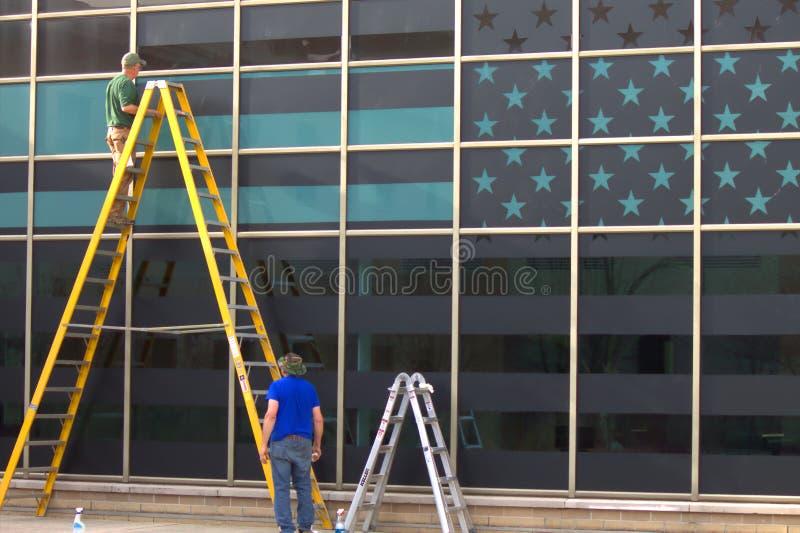 Dos trabajadores y una bandera en la ventana foto de archivo libre de regalías