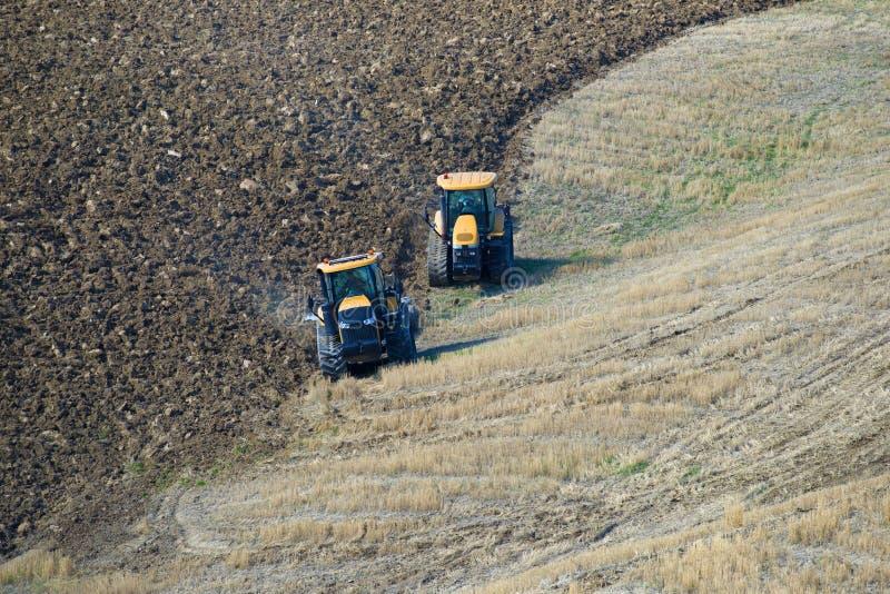 Dos tractores aran el campo con un día soleado de septiembre imágenes de archivo libres de regalías