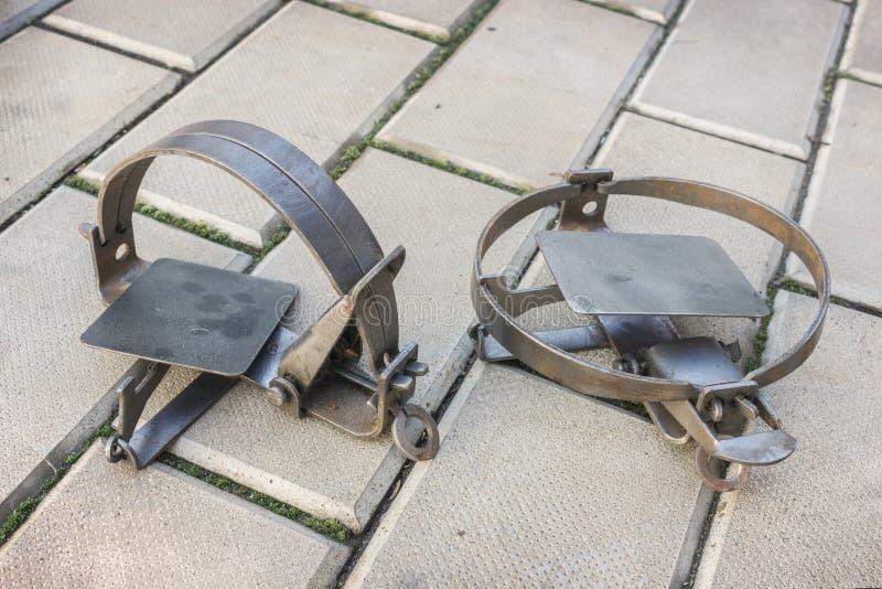Dos trampas oxidadas del hierro en el piso de piedra imagenes de archivo