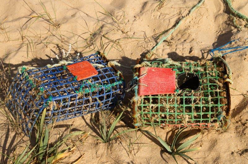 Dos trampas viejas del cangrejo en la arena de la playa foto de archivo libre de regalías