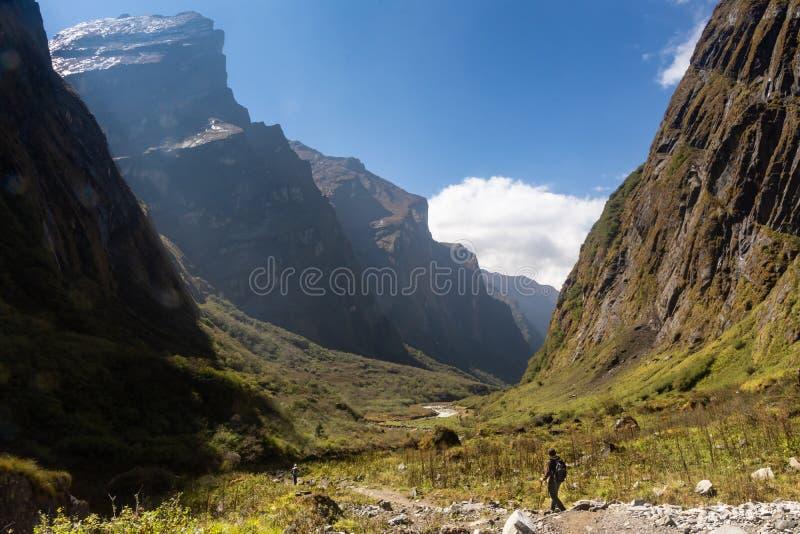 Dos trekkers que caminan a través del valle del glaciar en el senderismo del campo bajo de Annapurna imagenes de archivo