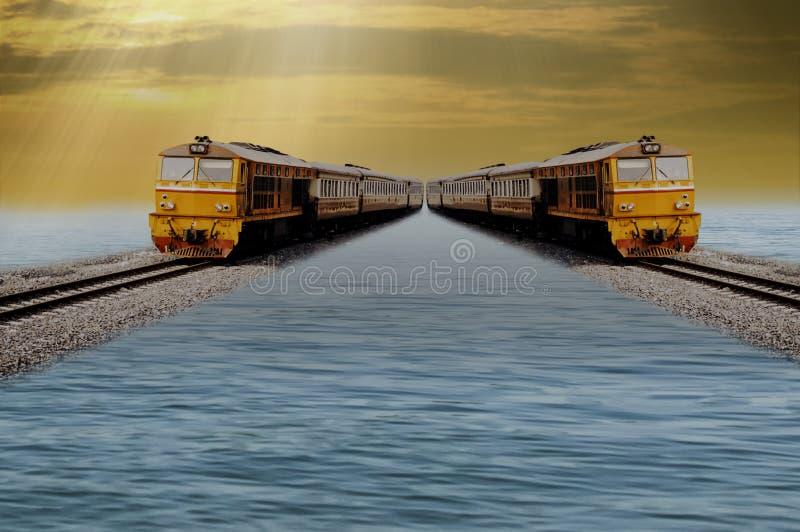 Dos trenes funcionan con paralelo al carril, flotando sobre el agua, cielo de la tarde del fondo, alrededores hermosos fotografía de archivo