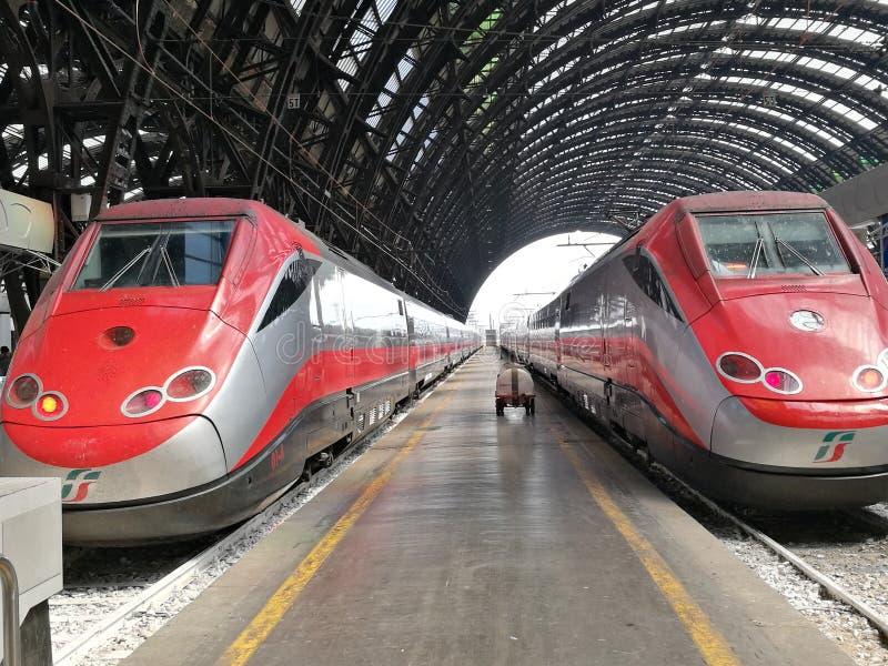 Dos trenes rojos en la parada en el ferrocarril antiguo de Milán Italia fotos de archivo