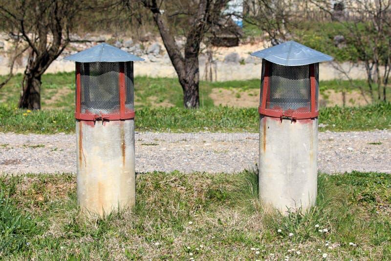 Dos tubos concretos viejos de la ventilación cubiertos con la malla metálica protectora rodeada con la hierba y la grava sin cort foto de archivo libre de regalías