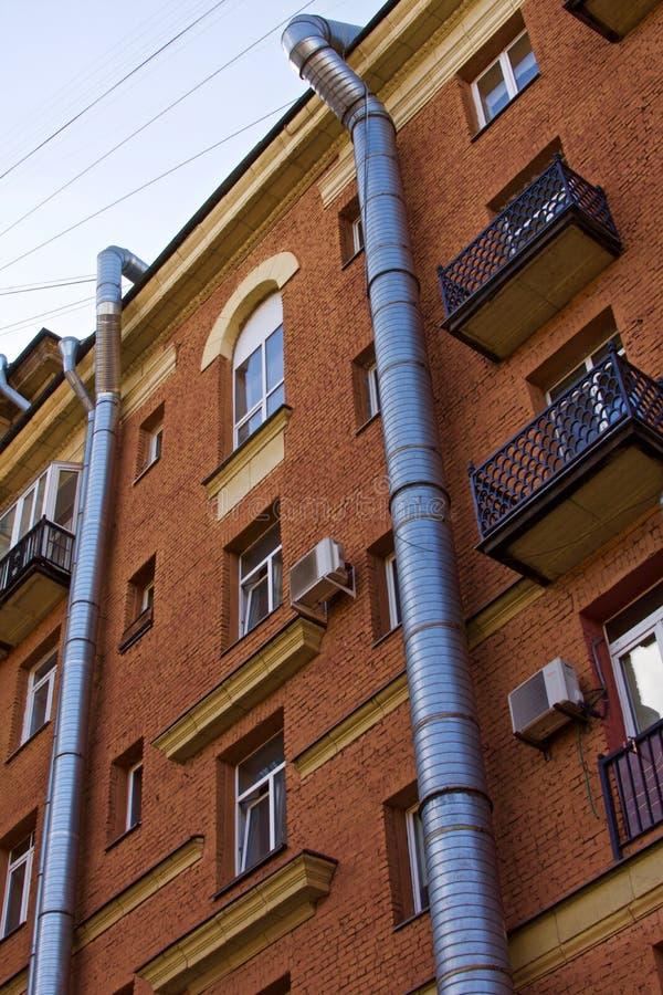 Dos tubos de ventilación del aire del metal funcionados con a lo largo de la fachada de un edificio de ladrillo fotografía de archivo