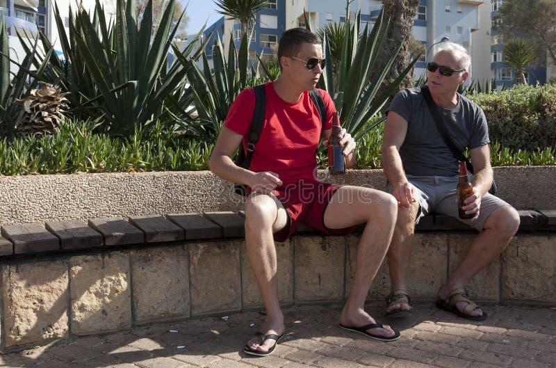 Dos turistas de diversas edades beben la cerveza y la charla que se sientan en un banco imagenes de archivo