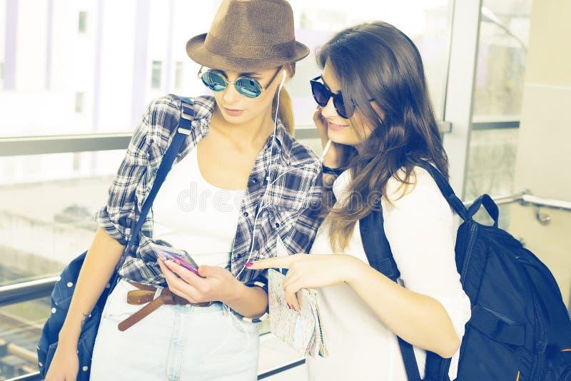 Dos turistas de las mujeres jovenes que miran el mapa y el mapa están en el terminal fotos de archivo libres de regalías