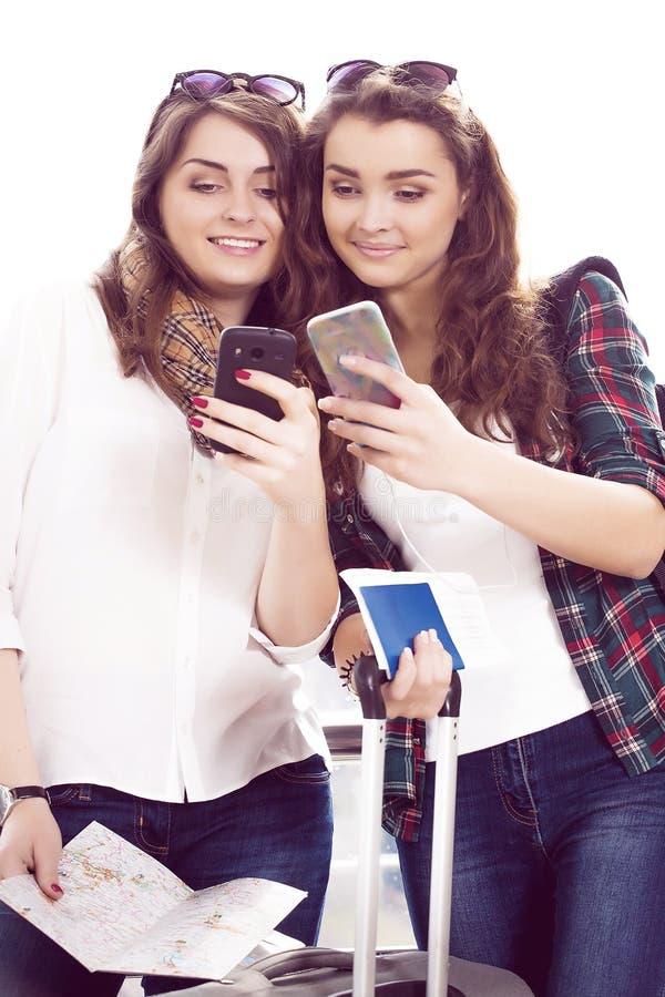 Dos turistas de las mujeres jovenes que sostienen un pasaporte y hacen el terminal del selfie fotografía de archivo
