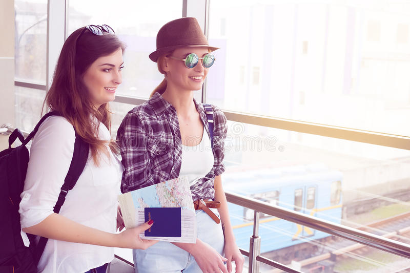 Dos turistas de las mujeres jovenes que sostienen una tarjeta y un pasaporte y están en el terminal fotos de archivo libres de regalías