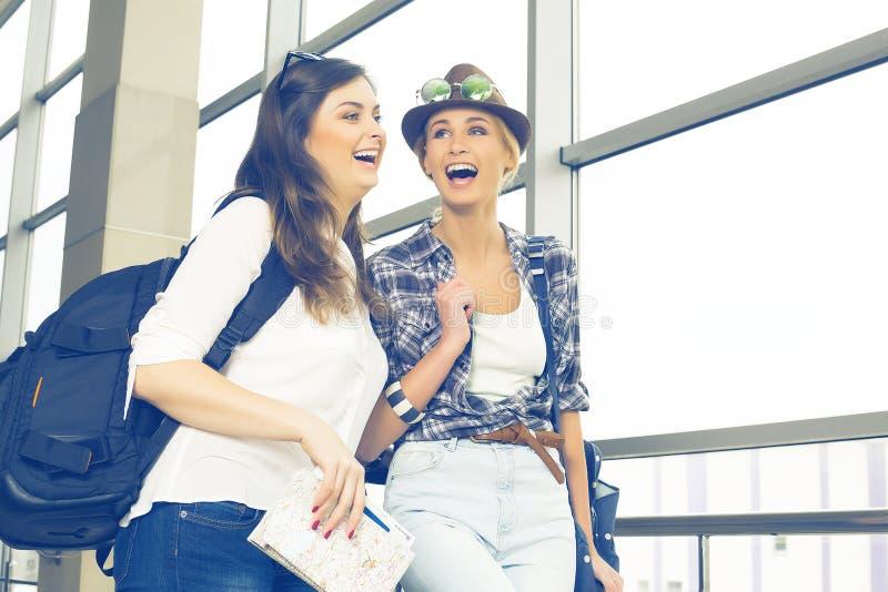 Dos turistas de las mujeres jovenes que sostienen una tarjeta y un pasaporte y están en el terminal imagen de archivo libre de regalías