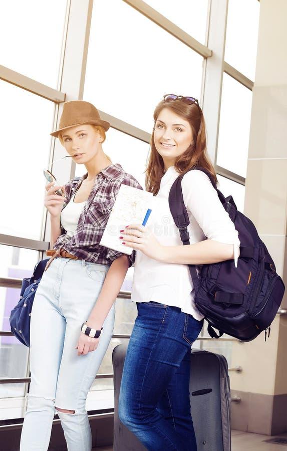 Dos turistas de las mujeres jovenes que sostienen una tarjeta y un pasaporte y que miran la cámara fotografía de archivo libre de regalías
