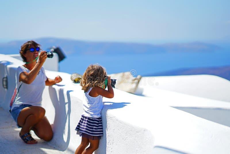 Dos turistas femeninos, madre e hija, toman las fotografías de Oia, en Santorini fotografía de archivo libre de regalías
