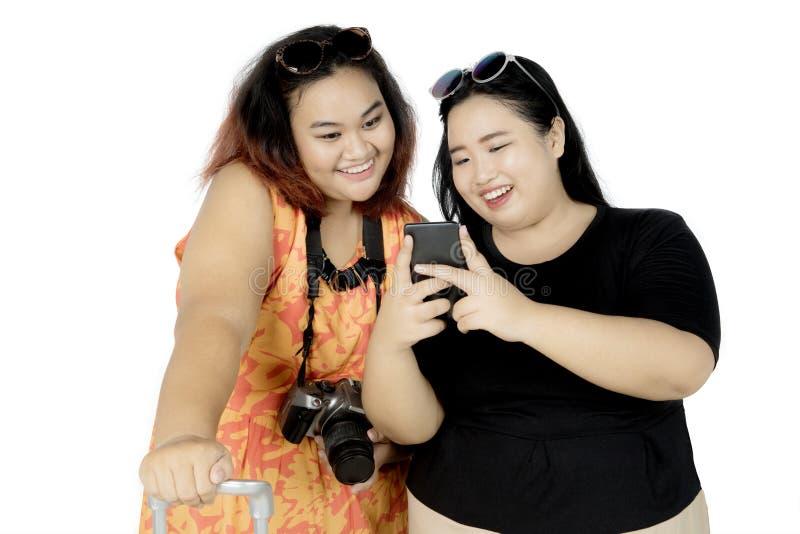 Dos turistas gordos que usan un smartphone en estudio foto de archivo