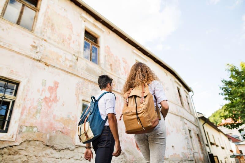 Dos turistas jovenes con las mochilas en la ciudad vieja imagenes de archivo