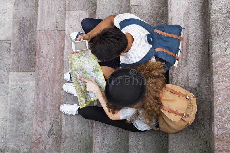 Dos turistas jovenes con smartphone en la ciudad vieja fotos de archivo