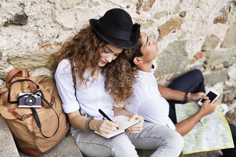 Dos turistas jovenes con un smartphone en la ciudad vieja fotos de archivo libres de regalías