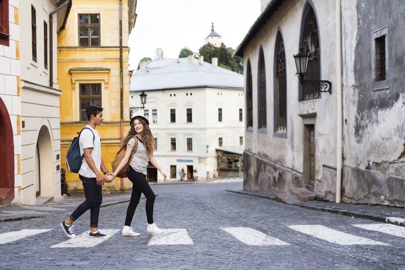Dos turistas jovenes que cruzan el camino en la ciudad vieja imagen de archivo libre de regalías