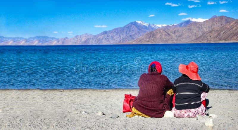 Dos turistas que se sientan al lado del lago en soledad durante el día delante de las aguas azules y de las montañas distantes fotografía de archivo