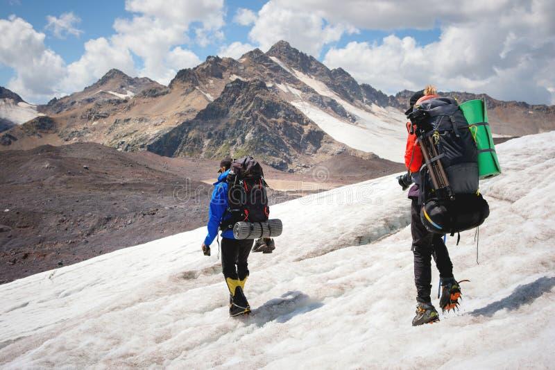 Dos turistas, un hombre y una mujer con las mochilas y los grampones en sus pies caminan a lo largo del glaciar contra el fondo imagen de archivo libre de regalías