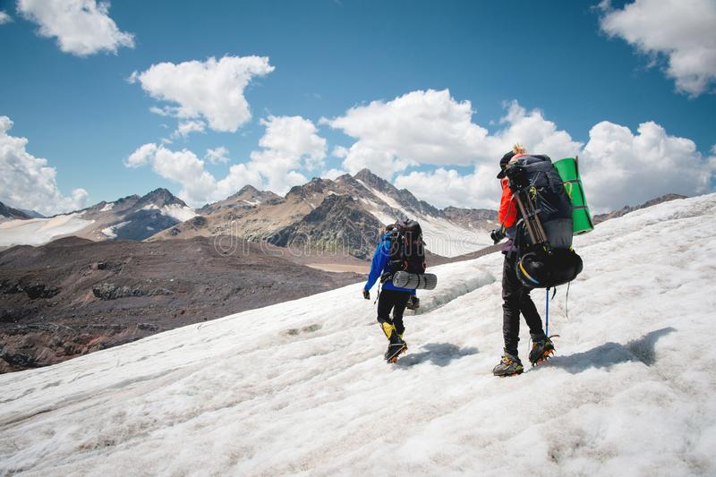 Dos turistas, un hombre y una mujer con las mochilas y los grampones en sus pies caminan a lo largo del glaciar contra el fondo fotografía de archivo