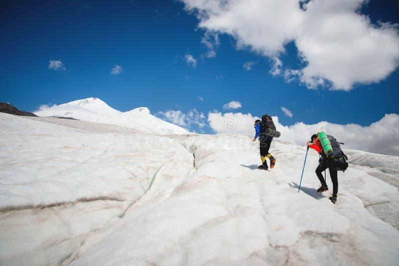 Dos turistas, un hombre y una mujer con las mochilas y los grampones en sus pies caminan a lo largo del glaciar contra el fondo imágenes de archivo libres de regalías