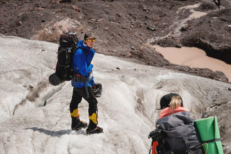 Dos turistas, un hombre y una mujer con las mochilas y los grampones en sus pies caminan a lo largo del glaciar contra el fondo foto de archivo