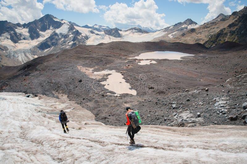 Dos turistas, un hombre y una mujer con las mochilas y los grampones en sus pies caminan a lo largo del glaciar contra el fondo imagenes de archivo