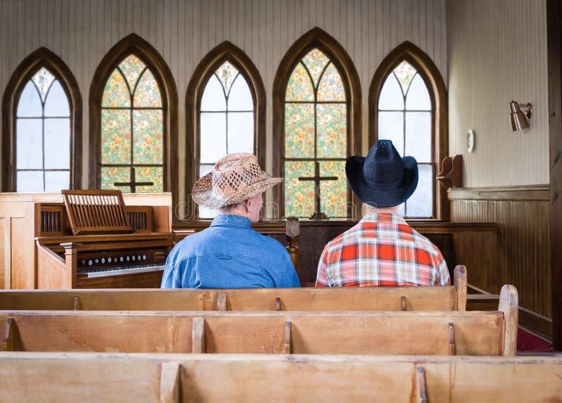 Dos vaqueros que se sientan junto en un banco de la iglesia foto de archivo
