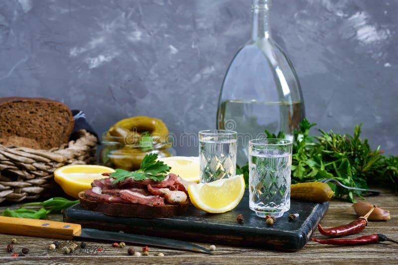 Dos vasos de medida de vodka con el limón cortan, conservaron en vinagre los pepinos y el pan de centeno con tocino salado fotografía de archivo