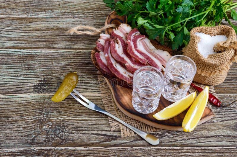 Dos vasos de medida de vodka con el limón cortan, conservaron en vinagre los pepinos y el pan de centeno con tocino salado en el  foto de archivo