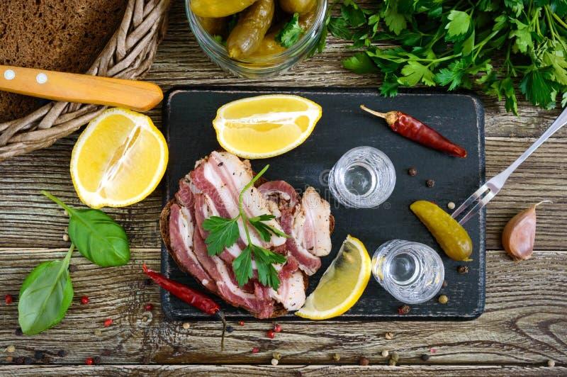 Dos vasos de medida de vodka con el limón cortan, conservaron en vinagre los pepinos y el pan de centeno con tocino salado en el  foto de archivo libre de regalías