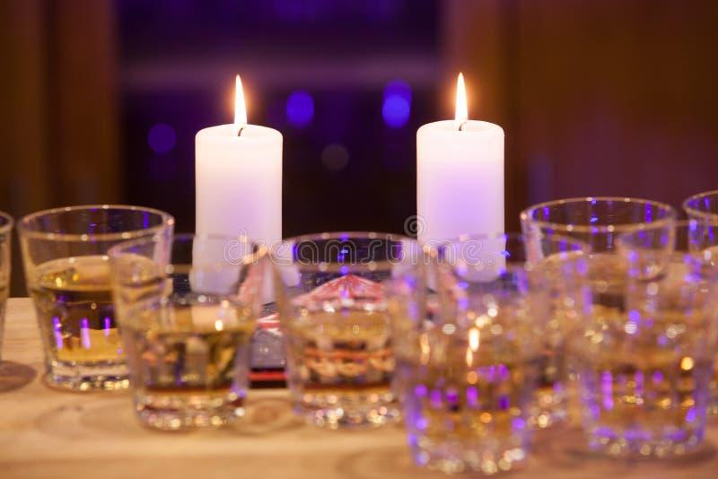 Dos velas ardientes en la tabla con los vidrios imagen de archivo libre de regalías