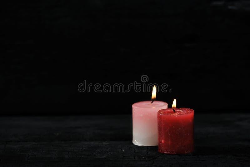 Dos velas con el fuego encendido en fondo negro fotos de archivo