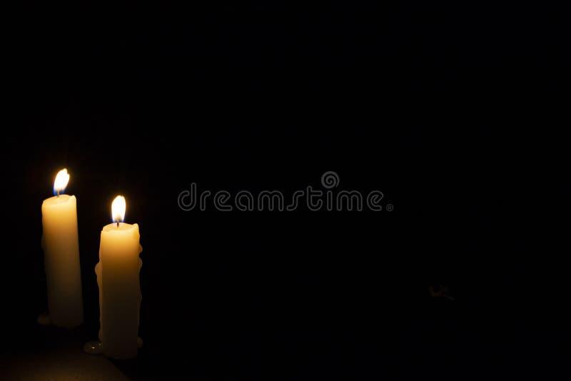 Dos velas en fondo oscuro Iluminación de velas en negro Vela amarilla de la cera con la llama caliente imagen de archivo libre de regalías