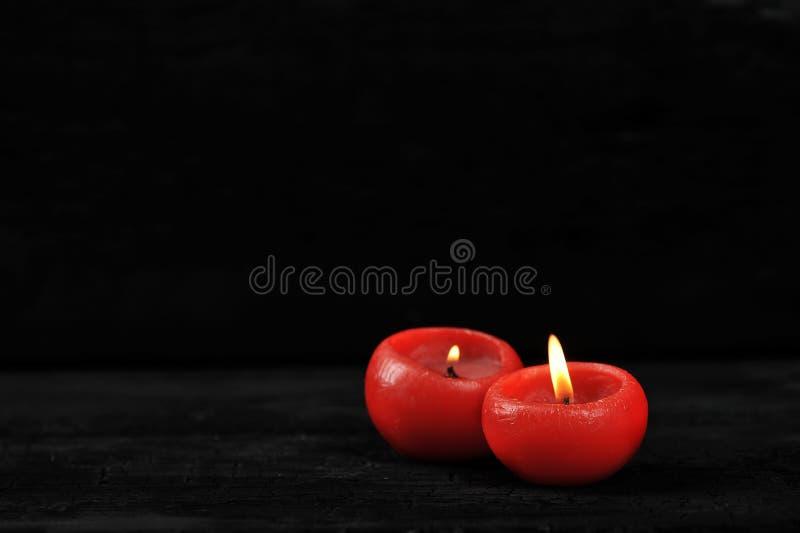 Dos velas rojas con el fuego encendido en fondo negro fotos de archivo