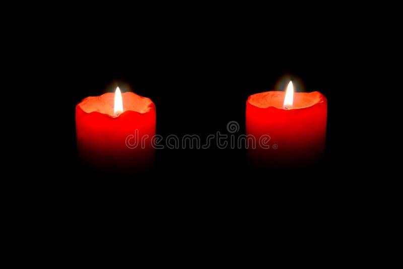Dos velas rojas que queman en la oscuridad fotos de archivo