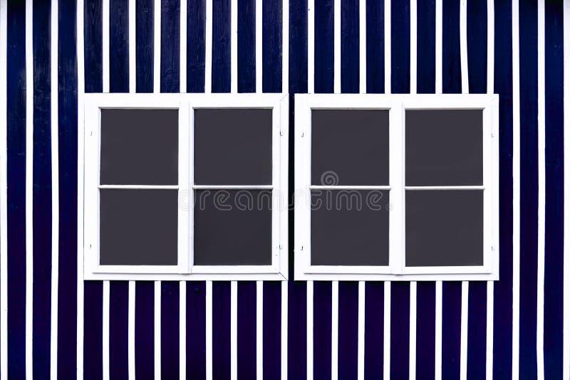 Dos ventanas blancas dobles en una pared azul con los listones blancos fotografía de archivo libre de regalías