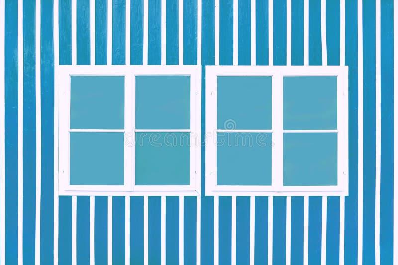 Dos ventanas blancas dobles en una pared azul con los listones blancos imagen de archivo libre de regalías