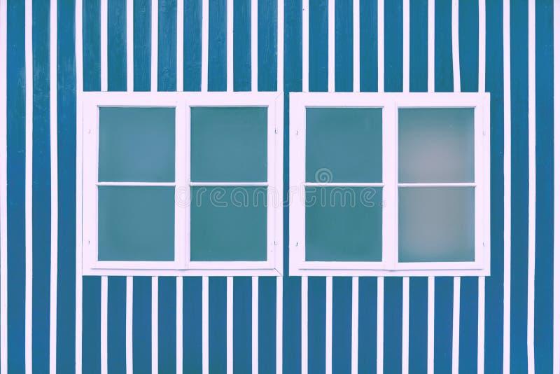 Dos ventanas blancas dobles en una pared azul con los listones blancos imagen de archivo