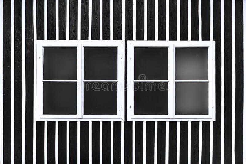 Dos ventanas blancas dobles en una pared negra con los listones blancos fotografía de archivo