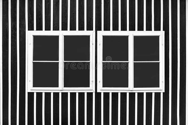 Dos ventanas blancas dobles en una pared negra con los listones blancos imagenes de archivo