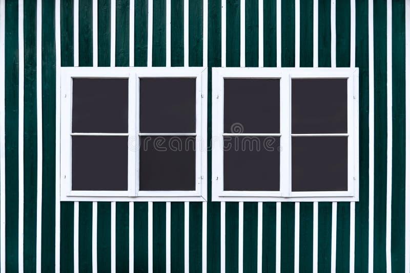 Dos ventanas blancas dobles en una pared verde con los listones blancos imágenes de archivo libres de regalías