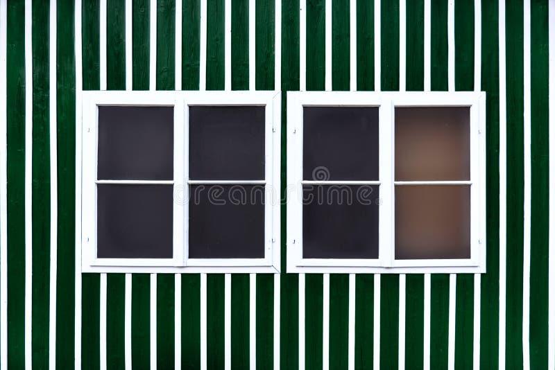 Dos ventanas blancas dobles en una pared verde con los listones blancos fotos de archivo
