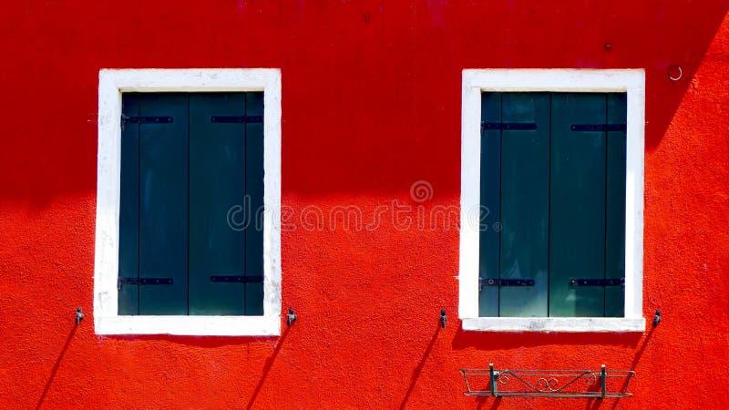 Dos ventanas con el marco blanco en la pared del color rojo foto de archivo
