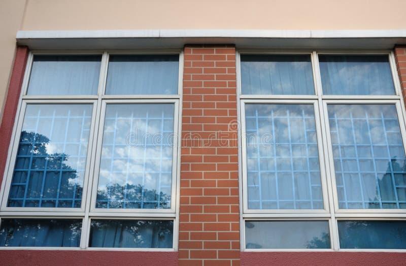 Dos ventanas con la reflexión de los cielos azules azules en los cristales fotografía de archivo libre de regalías