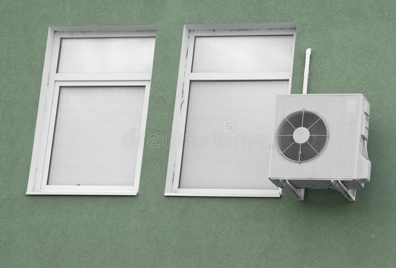 Dos ventanas con las persianas blancas y la aire-condición imagenes de archivo