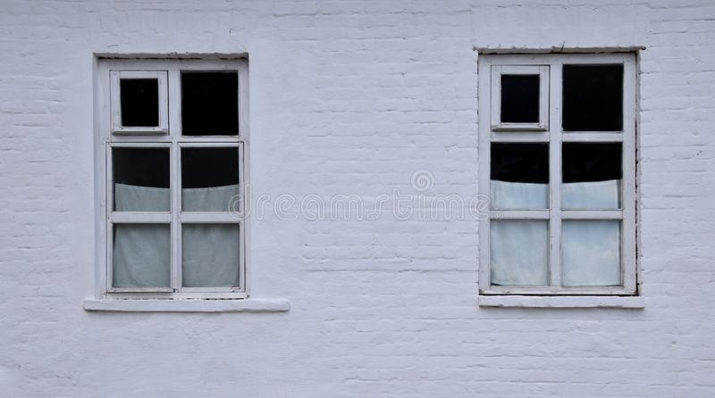 Dos ventanas de la ciudad con las cortinas blancas imagenes de archivo