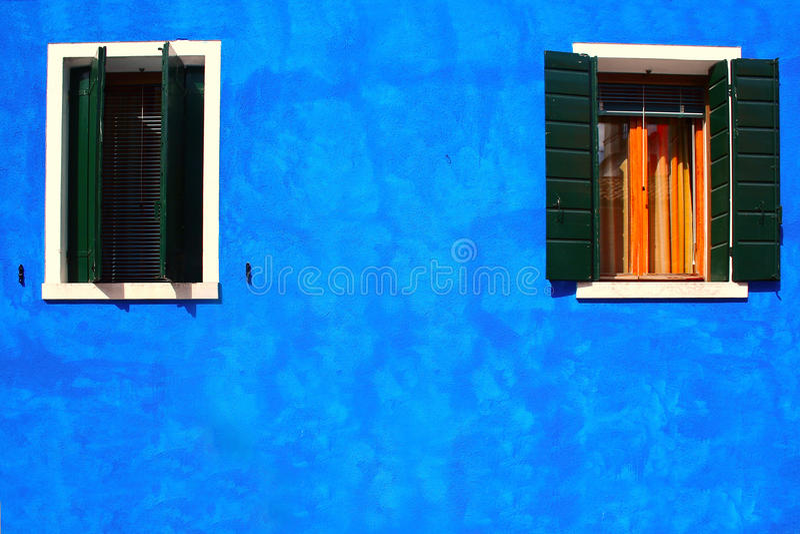 Dos ventanas en casa azul en la isla del burano fotos de archivo
