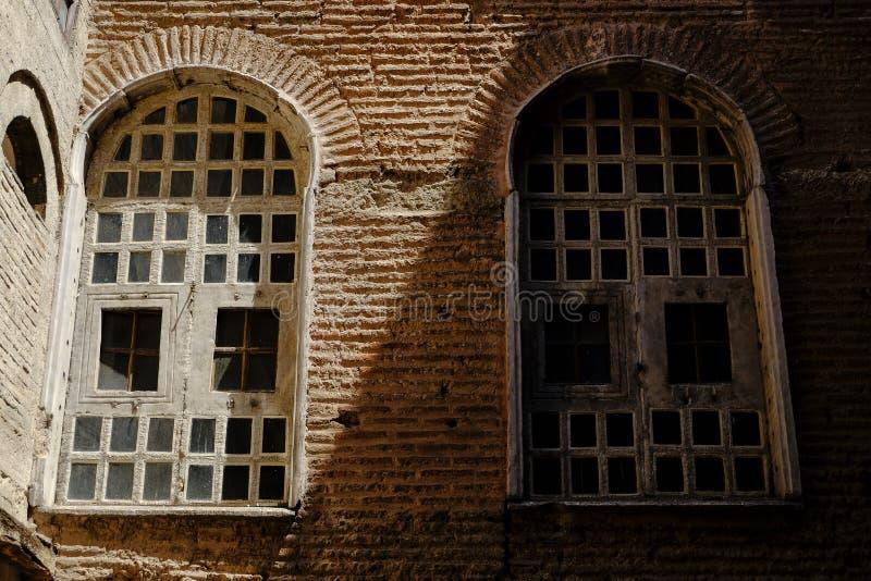 Dos ventanas en sombra y luz en la pared de ladrillo de la teja imagen de archivo libre de regalías