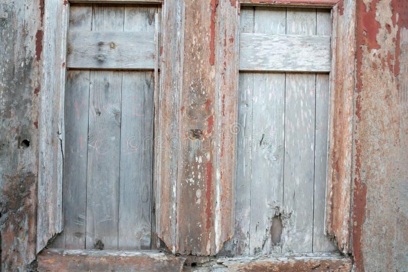 Dos ventanas viejas en la casa rural destruida en viejo rojo agrietado de madera y blanco pintados imagen de archivo